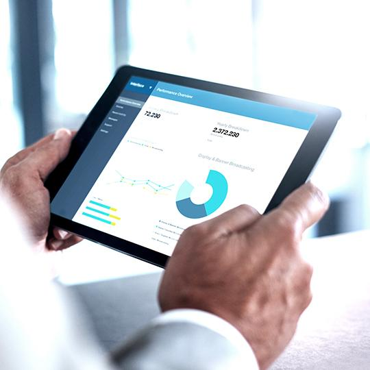 close up of man holding a tablet with a graph on the screen